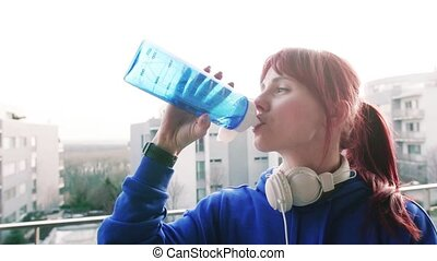 Young fitness woman drinking water on a balcony at home.