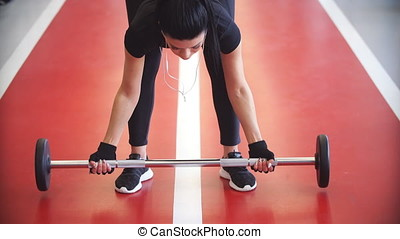 Young fitness woman exercise with barbells in gym for building muscles.