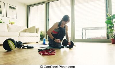 Young fitness woman getting ready for exercise at home. - An...