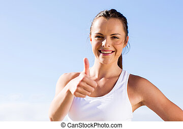young fitness woman giving thumbs up