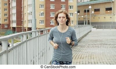 Young fitness woman having an exercise run in a residential area super slow motion