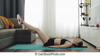 Young fitness woman in athletic workout clothes doing exercise from mat while using a stopwatch on her smartphone. She is training at home. Healthy and sport lifestyle.