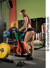 young fitness woman in gym