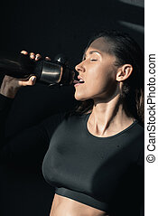 Young fitness woman in sportswear drinking water with closed eyes