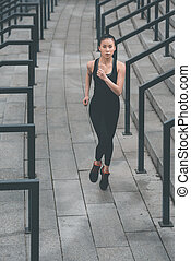 Young fitness woman in sportswear running on stadium stairs