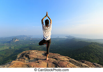 young fitness woman meditating on mountain peak
