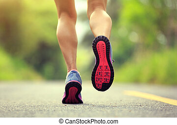 Young fitness woman runner legs running on forest trail