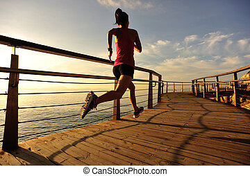 young fitness woman runner running at seaside boardwalk