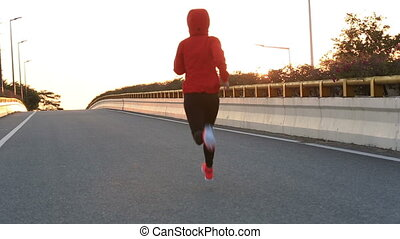 young fitness woman runner running on sunrise road Done