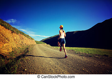 young fitness woman runner running on mountain trail