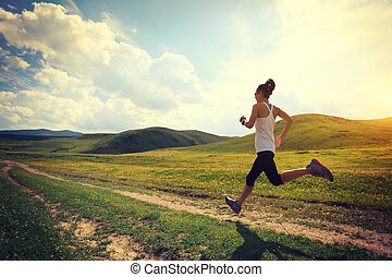 young fitness woman runner running on grassland trail