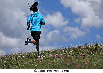 young fitness woman runner running on grassland