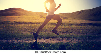 young fitness woman runner running on sunset trail