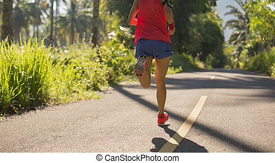 young fitness woman runner running on the forest trail