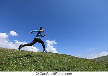 young fitness woman runner running jumping on grassland