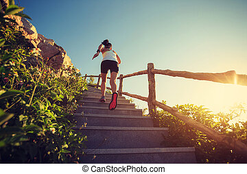young fitness woman runner running upstairs on mountain...