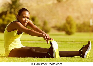 Young fitness woman runner stretching legs in the park