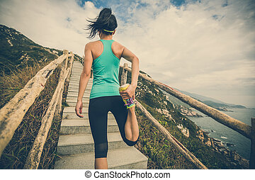 young fitness woman runner stretching legs on mountain trail