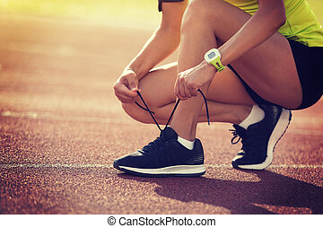 Young fitness woman runner tying shoelace on stadium