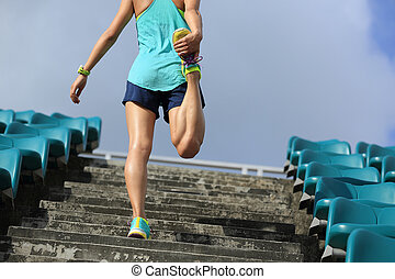 young fitness woman runner warm up on stairs