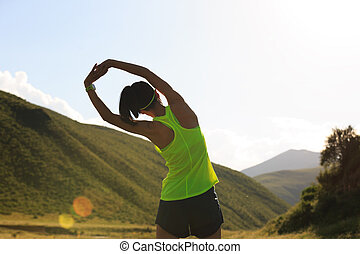 young fitness woman runner warming up on grassland trail