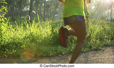 Young fitness woman running at tropical forest trail