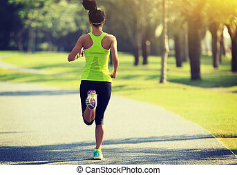 Young fitness woman running at tropical park