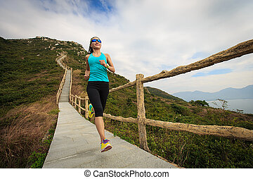 young fitness woman running on mountain trail