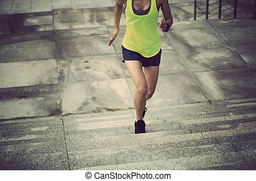 Young fitness woman running up on city stairs