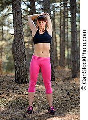 Young Fitness Woman Stretching in the Pine Forest. Female Runner Doing Stretches . Healthy Lifestyle Concept.