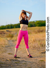 Young Fitness Woman Stretching in the Wild Park. Female Runner Doing Stretches . Healthy Lifestyle Concept.