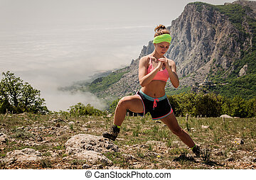 young fitness woman stretching legs on mountain