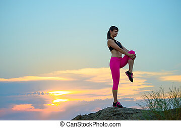 Young Fitness Woman Stretching on the Top of Rock. Female Runner Doing Stretches . Healthy Lifestyle Concept.