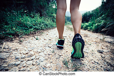 young fitness woman trail runner legs running on forest