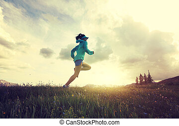 young fitness woman trail runner running on beautiful...