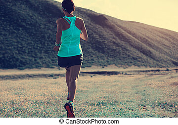 young fitness woman trail runner running on mountain grassland