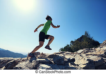 young fitness woman trail runner running on top of mountain