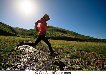 young fitness woman trail runner running outdoors