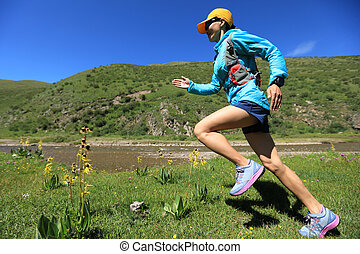young fitness woman trail runner running on riverside trail