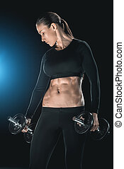 young fitness woman training with dumbbells isolated on black.