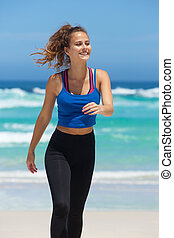 Young fitness woman walking on beach