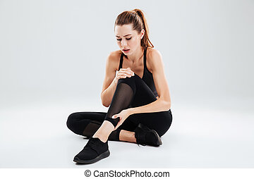 Young fitness woman with an ankle pain sitting
