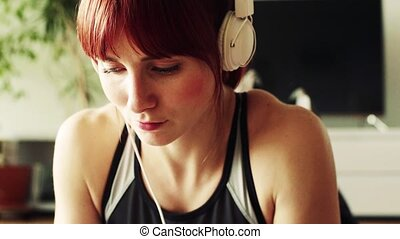 Young fitness woman with headphones at home, listening to music.
