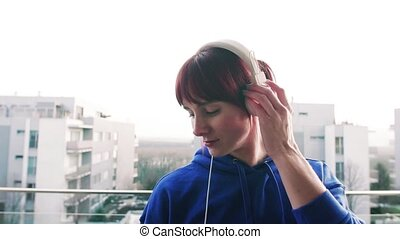 Young fitness woman with headphones on a balcony at home. -...