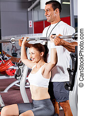 young fitness woman with personal trainer