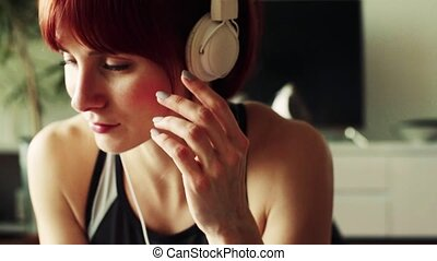Young fitness woman with smartphone and headphones at home.
