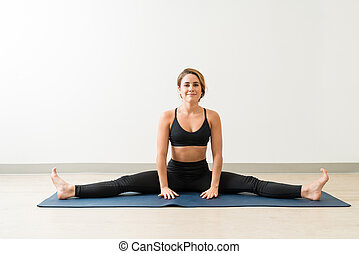 Portrait of beautiful smiling woman relaxing while doing straddle splits on mat against wall during workout