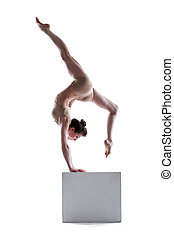 Young flexible woman posing on cube