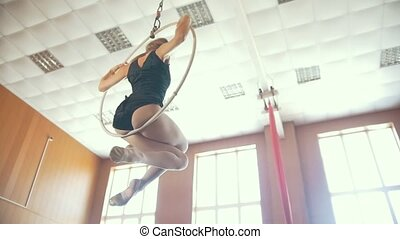 Young flexible woman twirling on the aerial hoop in studio,...