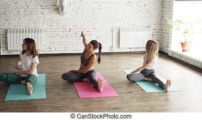Young flexible women are doing various stretching exercises sitting on yoga mats in nice light studio. They are bending head or chest to knee concentrated on breathing.